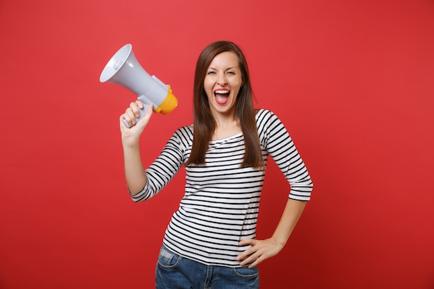 Cheerful young woman in striped clothes holding megaphone, keeping mouth wide open, screaming isolated on bright red wall background. people sincere emotions, lifestyle concept. mock up copy space.