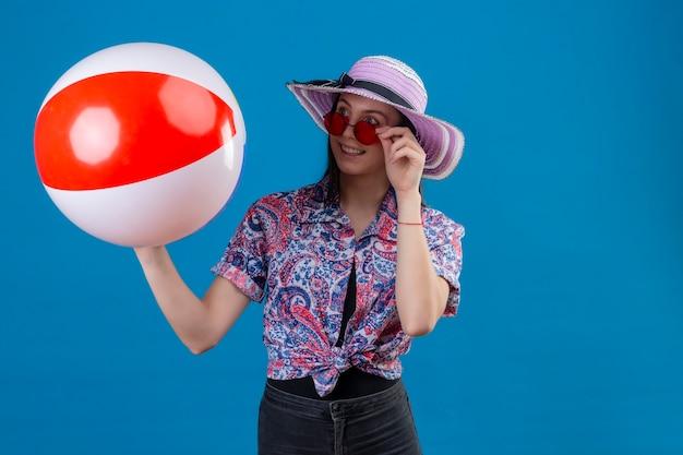 Giovane donna allegra in cappello di estate che indossa occhiali da sole rossi che tengono palla gonfiabile che osserva da parte con il sorriso felice che sta sopra lo spazio blu