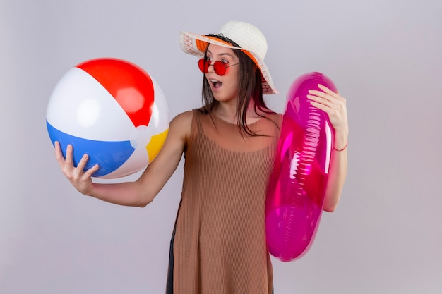 Cheerful young woman in summer hat wearing red sunglasses holding inflatable ring and ball looking at it surprised and happy standing