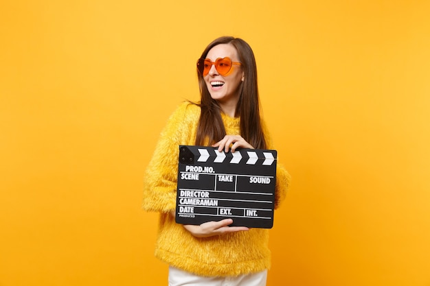 Cheerful young woman in sweater orange heart eyeglasses looking aside holding classic black film making clapperboard isolated on yellow background. people sincere emotions lifestyle. advertising area.