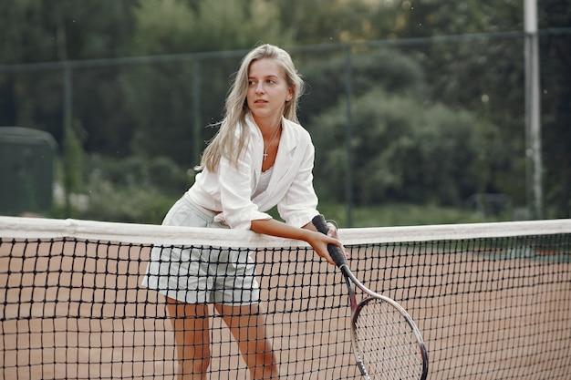 Giovane donna allegra in maglietta. donna che mantiene racchetta da tennis e palla.