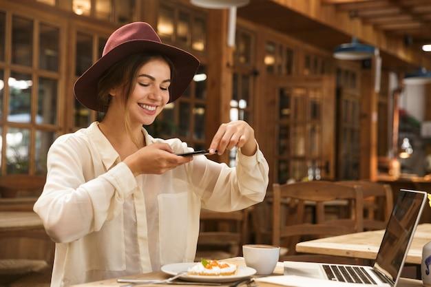 彼女の昼食の写真を撮る陽気な若い女性