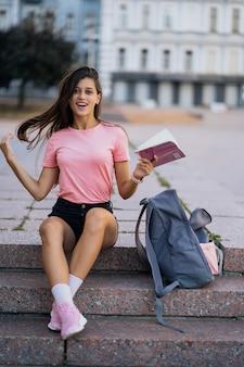 Веселая молодая женщина делает заметки, сидя на ступеньках