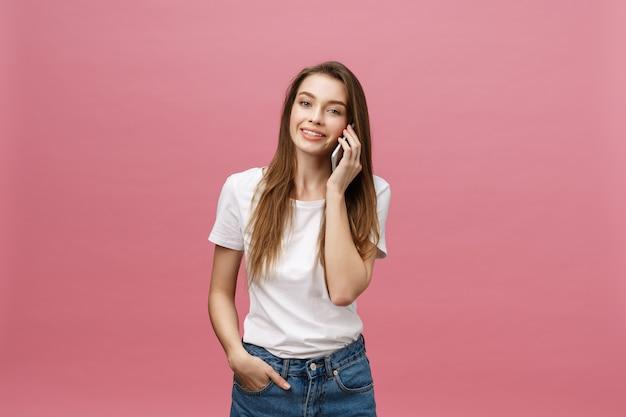 Веселая молодая женщина разговаривает по мобильному телефону