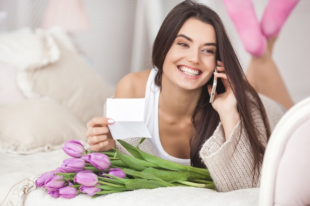 Cheerful young woman talking on the phone and holding flowers. beautiful lady with tulips