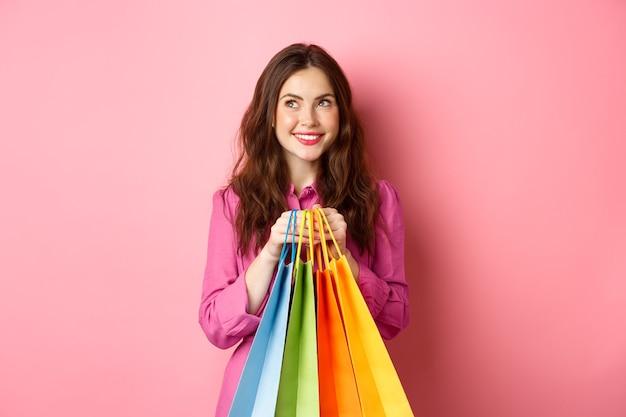 何かを買うことを考えている陽気な若い女性、夢のような笑顔で買い物袋を持って、スタッフを買う、ピンクの壁の上に立っています。