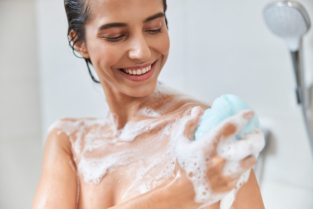 Cheerful young woman using exfoliating loofah while taking shower