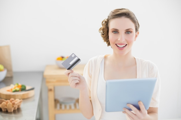 Cheerful young woman using her tablet for home shopping sitting in her kitchen