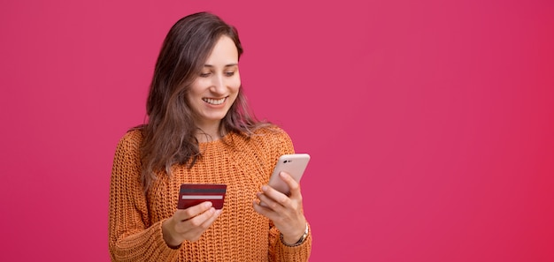 Cheerful young woman using his smartphone and holding credit card, mobile web banking