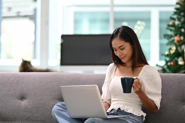 Веселая молодая женщина, использующая ноутбук, смотрит смешное видео и пьет кофе, сидя на диване в гостиной.
