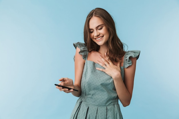 Cheerful young woman using mobile phone.
