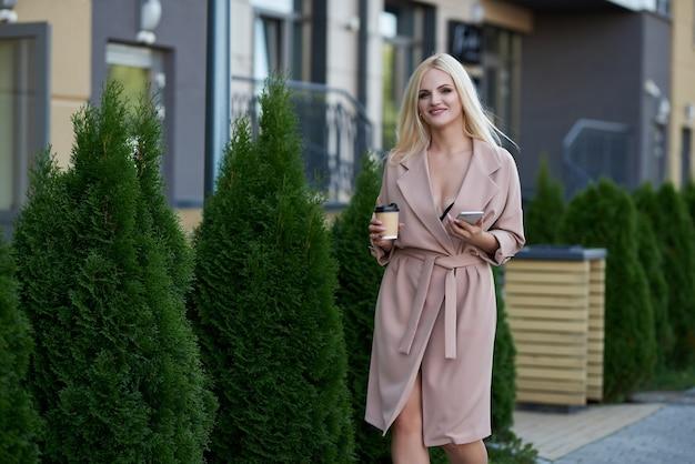 Веселая молодая женщина гуляет на открытом воздухе, держа чашку кофе на вынос, используя мобильный телефон