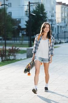 아침에 공원에서 스케이트보드를 들고 걷는 쾌활한 젊은 여성
