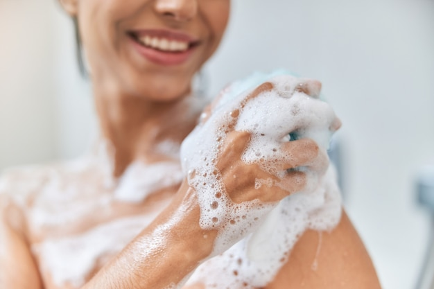 Cheerful young woman washing her body with bath loofah