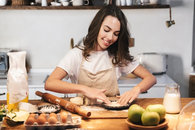 Cheerful young woman wearing apron preparing dough for an apple pie at the kitchen at home