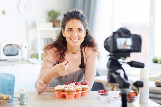 Cheerful young woman wearing apron tasting sweet strawberry on camera, horizontal portrait