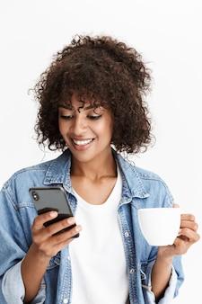 白い壁に隔離された椅子に座って、一杯のコーヒーを保持し、携帯電話を使用して、カジュアルなデニムの服を着ている陽気な若い女性