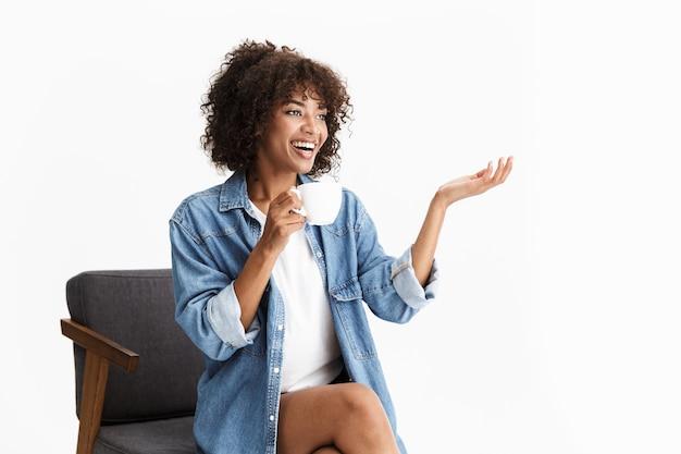 白い壁に隔離された椅子に座って、コーヒーのカップを保持しているカジュアルなデニムの服を着て陽気な若い女性