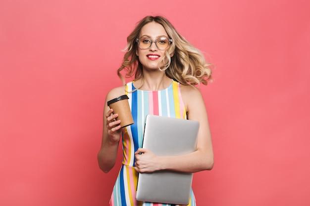 Веселая молодая женщина в очках, стоящая изолирована на красном фоне