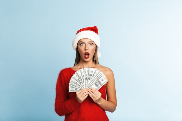 Cheerful young woman wearing santa claus hat, showing money banknotes
