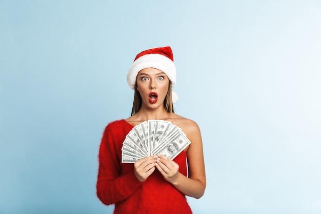 쾌활 한 젊은 여자 산타 클로스 모자를 쓰고 돈 지폐를 보여주는