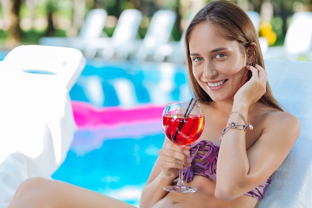 Веселая молодая женщина в стильных украшениях, лежа под солнцем возле открытого бассейна