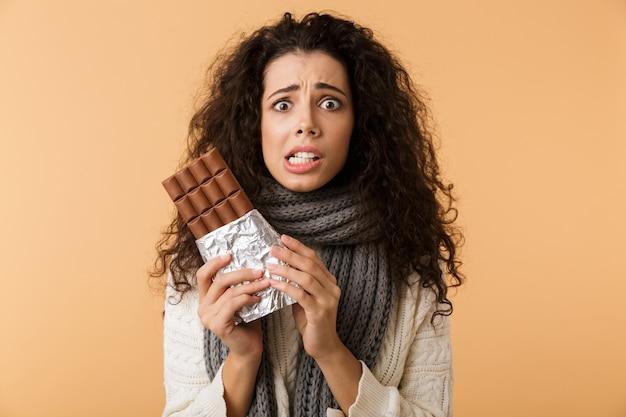 Веселая молодая женщина в свитере и шарфе держит большую плитку шоколада, изолированную над бежевой стеной