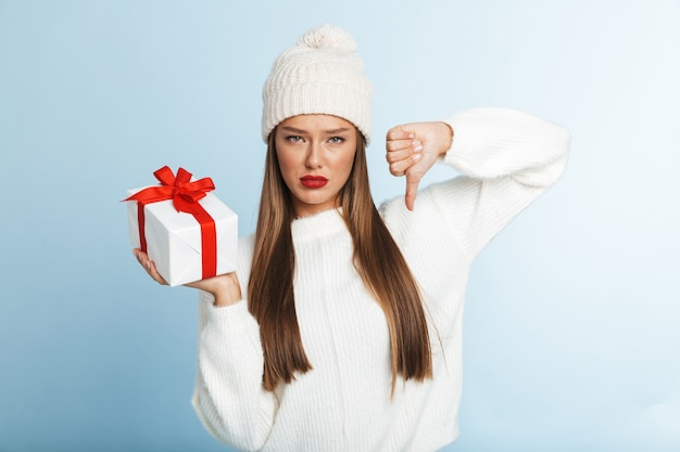 Cheerful young woman wearing sweater and hat, holding gift box, showing thumbs down