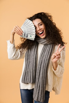 Cheerful young woman wearing winter scarf standing isolated over beige wall, holding money banknotes