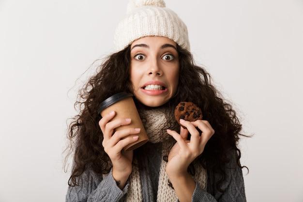 Веселая молодая женщина в зимнем шарфе стоит изолированно над белой стеной, держа на вынос чашку кофе и шоколадное печенье