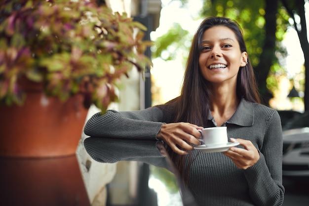 Веселая молодая женщина с чашкой кофе, сидя в кафе, улыбаясь на открытом воздухе