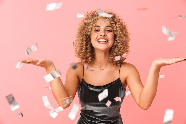 Cheerful young woman with curly hair, having fun under confetti shower