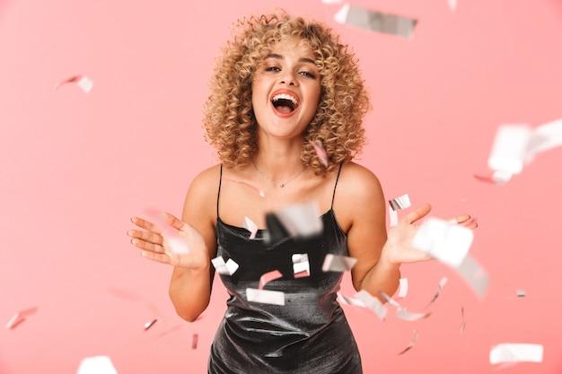 곱슬 머리를 가진 쾌활 한 젊은 여자, 색종이 샤워에서 재미