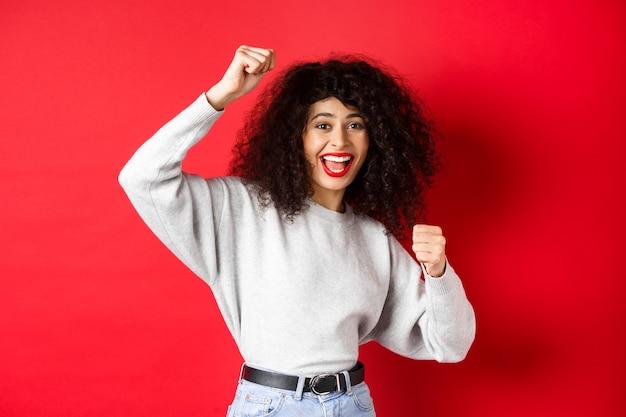 Жизнерадостная молодая женщина с вьющимися волосами, поднимая руку и празднуя победу, достигая цели или успеха, стоя на красном фоне.