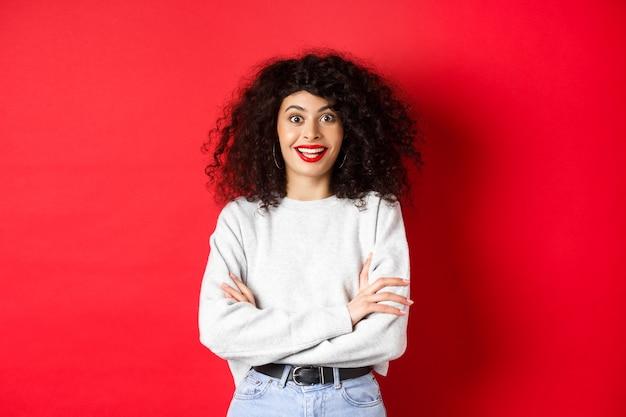 巻き毛の髪型、眉を上げて驚いて見える陽気な若い女性は、興味深いニュース、赤い背景を聞きます。