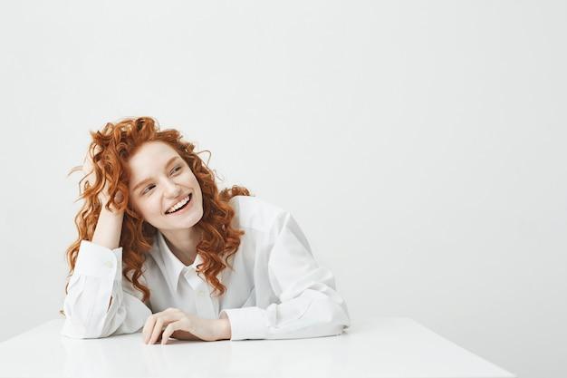 Жизнерадостная молодая женщина с foxy волосами, улыбаясь, смеясь сидя за столом.