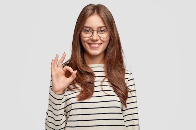 Веселая молодая женщина в очках позирует у белой стены