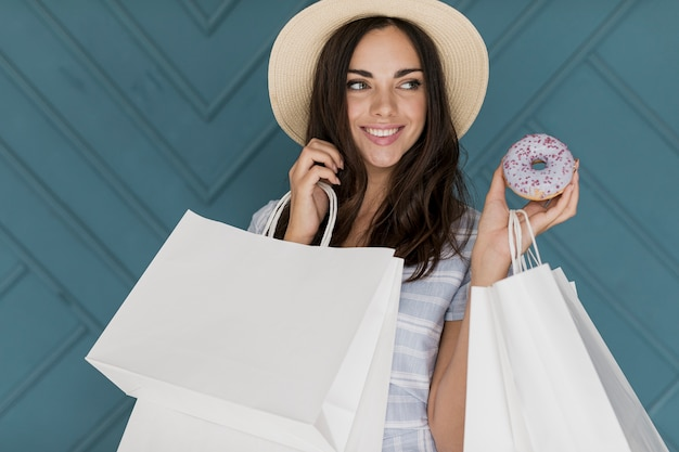 Cheerful young woman with hat and a donut