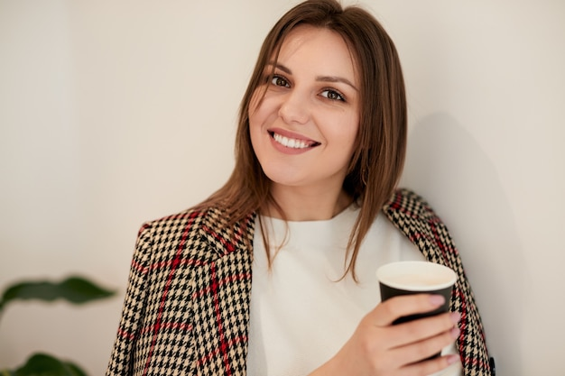 カフェで温かい飲み物と陽気な若い女性