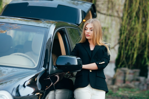 Cheerful young woman with luxury car