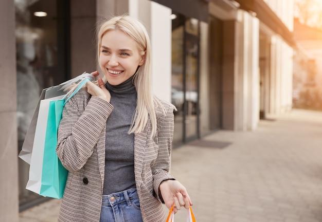 買い物をした後、街の通りの歩道に立っている間笑顔と目をそらしている紙袋を持つ陽気な若い女性