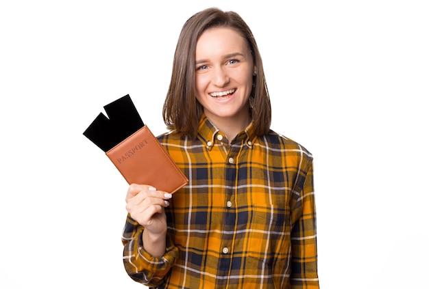 Веселая молодая женщина с паспортом и билетами