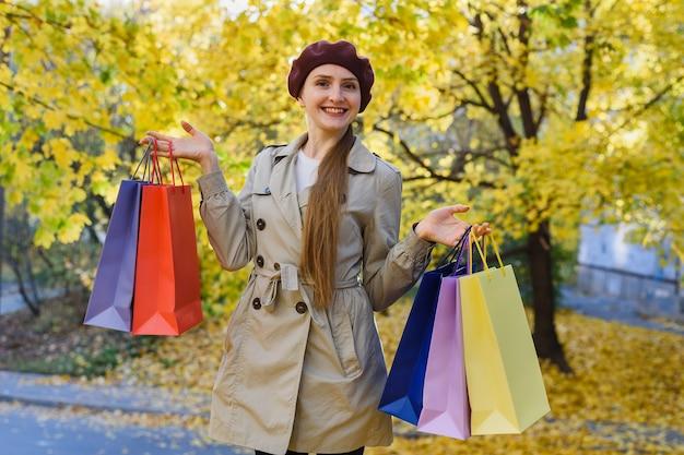 秋の公園で買い物袋を持つ陽気な若い女性