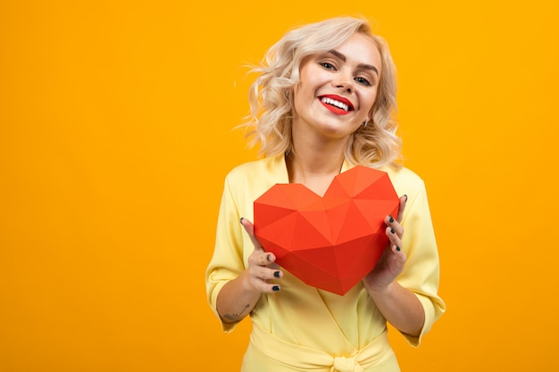 Cheerful young woman with short blonde hair smiles and holds a big red heart isolated on orange