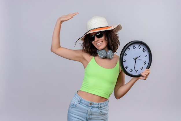 A cheerful young woman with short hair in green crop top wearing sunglasses and sun hat holding a wall clock and raising hand on a white background