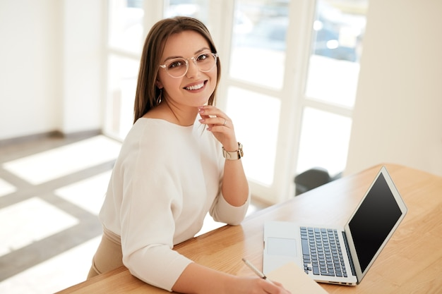 Cheerful young woman working on laptop in office in daylight
