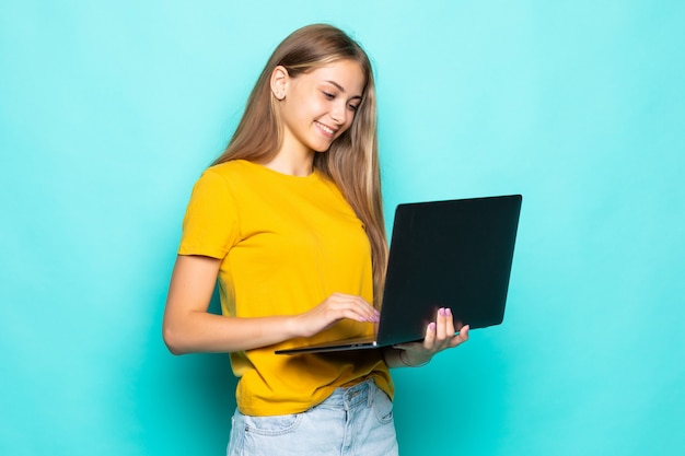 청록색 벽에 고립 된 노트북 포즈에서 작업하는 쾌활 한 젊은 여자