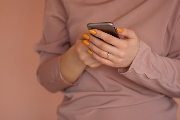 陽気な若い女性は彼女の携帯電話でテキストメッセージを書きます。スマートフォンを使用しているかなり若い女性。携帯電話を持って画面を見ている若いヒップスター。