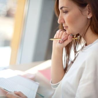 쾌활한 젊은 여자가 그녀의 개인 일일 일기 책을 쓰고 유지