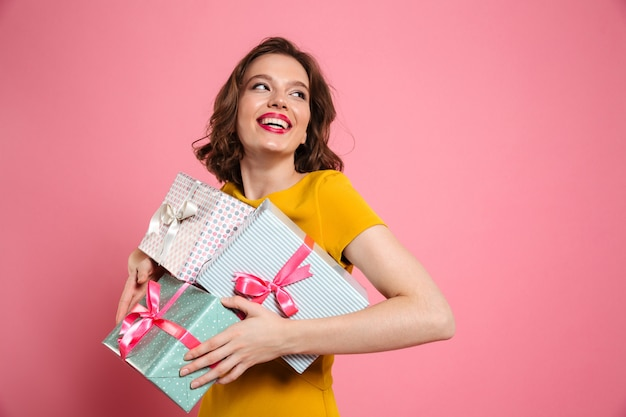 Cheerful young woman in yellow dress holding heap of presents